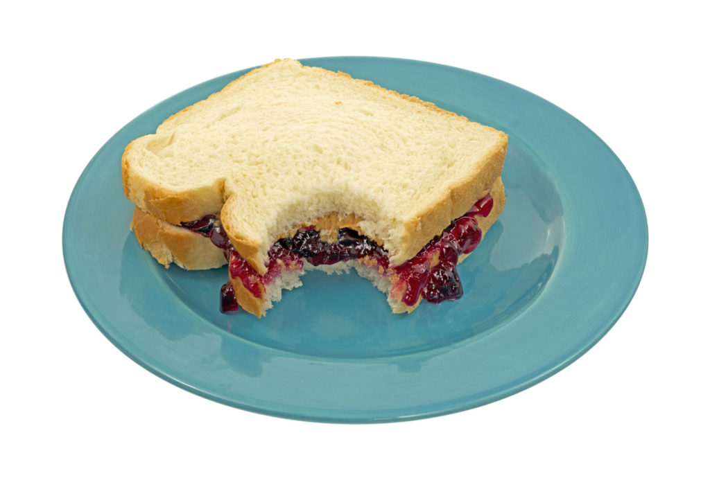 A peanut butter and jelly sandwich that has had one bite on a blue plate
